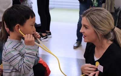 little boy listens to a nurse's stethescope